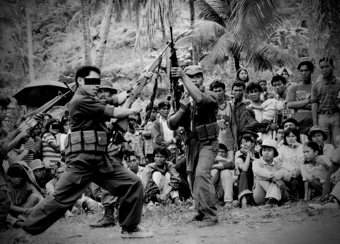 """IN PRAISE OF THE MASSES. """"Ang masa, ang masa lamang ang siyang tunay na bayani,"""" goes a line in the song  being sung while these Red fighters do an interpretative dance during  celebrations for the anniversary of the Communist Party of the  Philippines in Negros island more than a decade ago. 