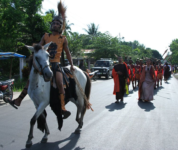 BACK IN TIME. A Roman centurion rides a horse while the cast of the Kalbaryo play walk behind him on their way to the multi-purpose activity center where the Kalbaryo play was held  | Photo by Julius D. Mariveles