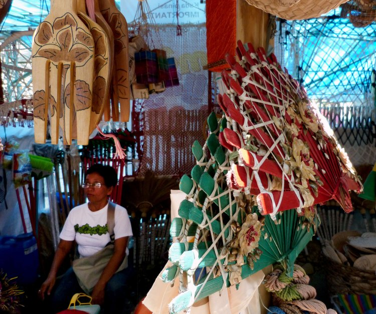 A WOMAN watches over her products - giant wooden forks and giant colored fans, among others - sold at one of the booths at the Panaad Park and Stadium in the village of Mansilingan, Bacolod City | Photo by Julius D. Mariveles